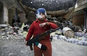 Ahmed a huit ans, fils d'un rebelle syrien pendant la guerre civile. Cet enfant monte la garde, AK-47 autour du cou, cigarette à la bouche dans les décombres de Alep (Syrie).